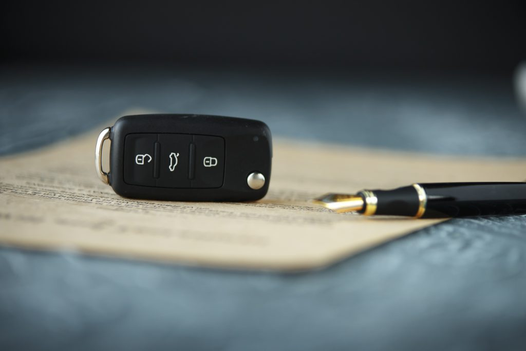 Privacy Help with buying a car Black car key on a signed contract