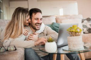 About us Young couple relaxing on couch with laptop. Love, happiness, people and fun concept